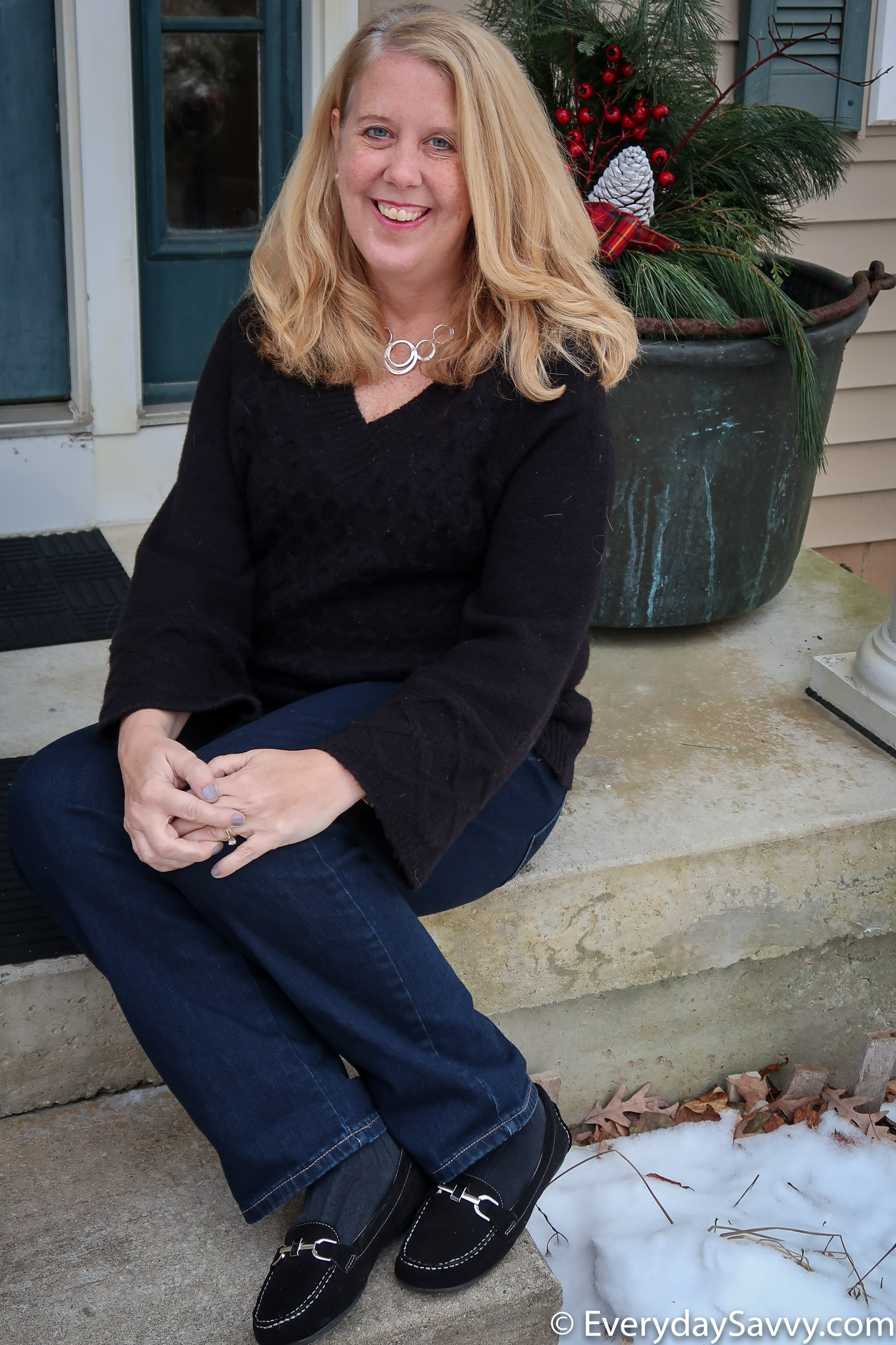 Cute Casual Holiday outfit - black sweater with bell sleeves, jeans and black loafers with silver detail
