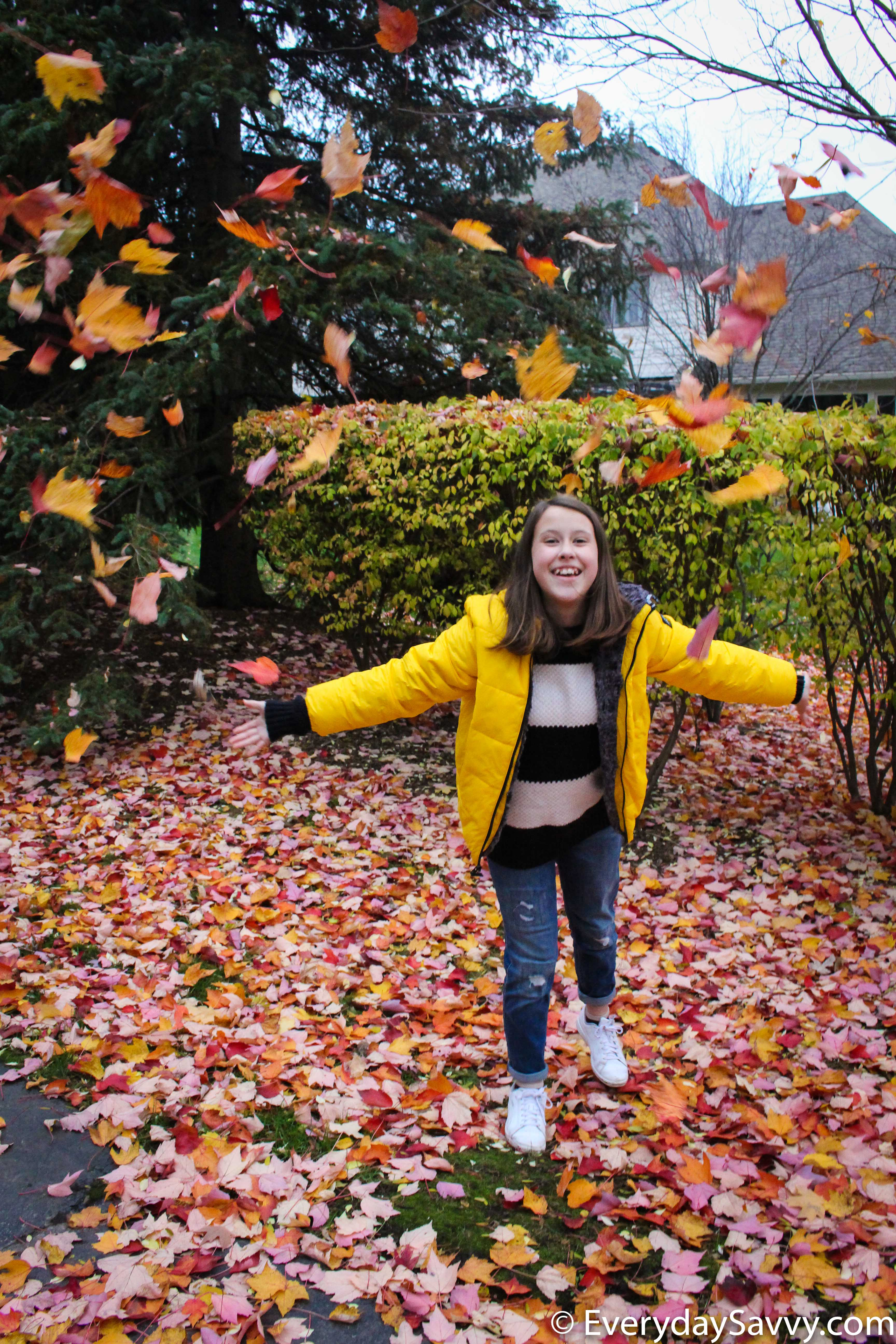 playing in the leaves with cute yellow coat
