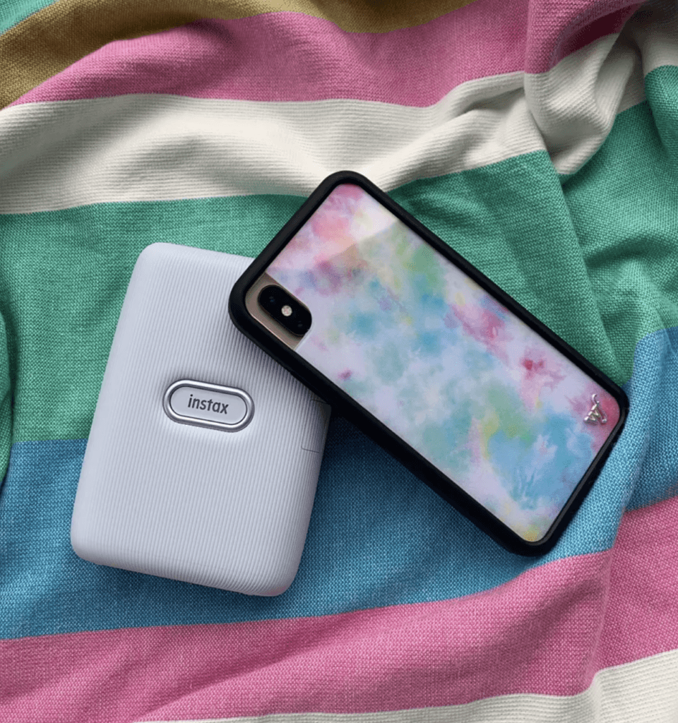 tie dye wildflower phone cases and instax on striped shirt