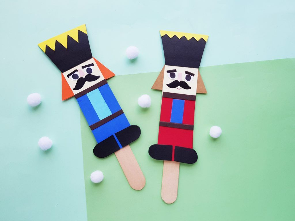 two nutcracker craft puppets on green and blue background